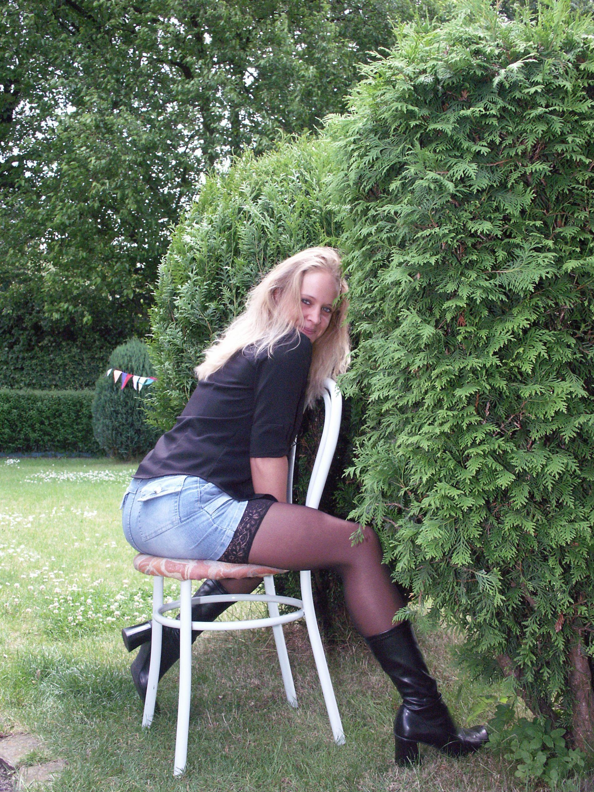 sexy Blondine halterlosen Strümpfen und Lederstiefeln sitzt auf Gartenstuhl