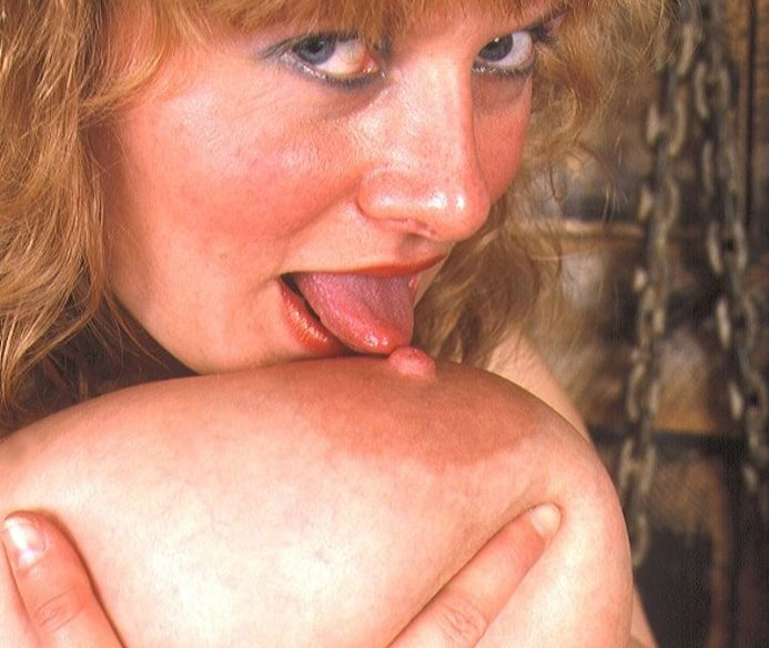 Dunkelblonde Frau lutscht an ihrer Riesentitte