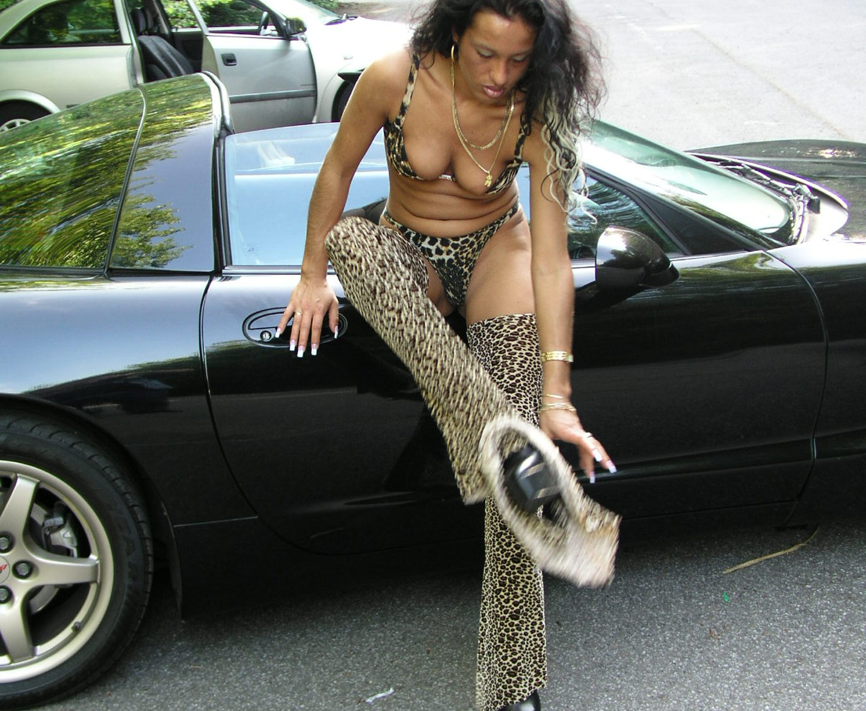 Leicht bekleidete Frau im Leporadenlook steht vor Cabrio